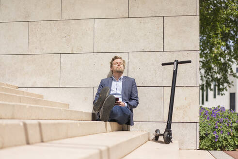 Businessman with E-Scooter and smartphone sitting on steps relaxing - JOSF03304