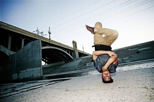 Mixed race man break dancing under overpass - BLEF07400