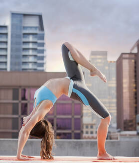 Caucasian woman practicing yoga on urban rooftop - BLEF07427
