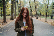 Young woman with long red hair looking at smartphone in tree lined autumn park, Florence, Tuscany, Italy - CUF51435