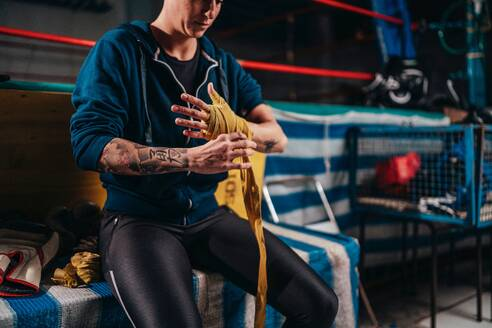 Boxer putting on handwrap in gym - ISF21495