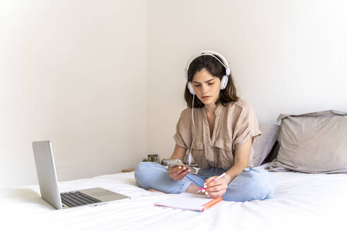 Young woman sitting on bed with headphones and laptop taking notes - AFVF03296