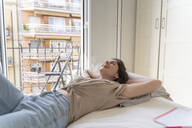 Happy young woman lying on bed with closed eyes - AFVF03302