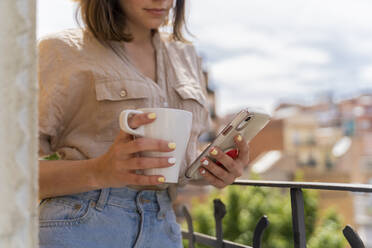 Close-up of woman on balcony in the city with coffee cup and cell phone - AFVF03311