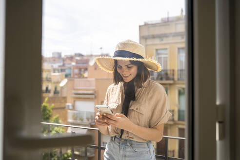 Smiling young woman on balcony in the city wearing straw hat using cell phone - AFVF03314