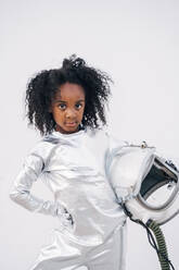 Portrait of little girl with space hat wearing space suit in front of white background - JCMF00068