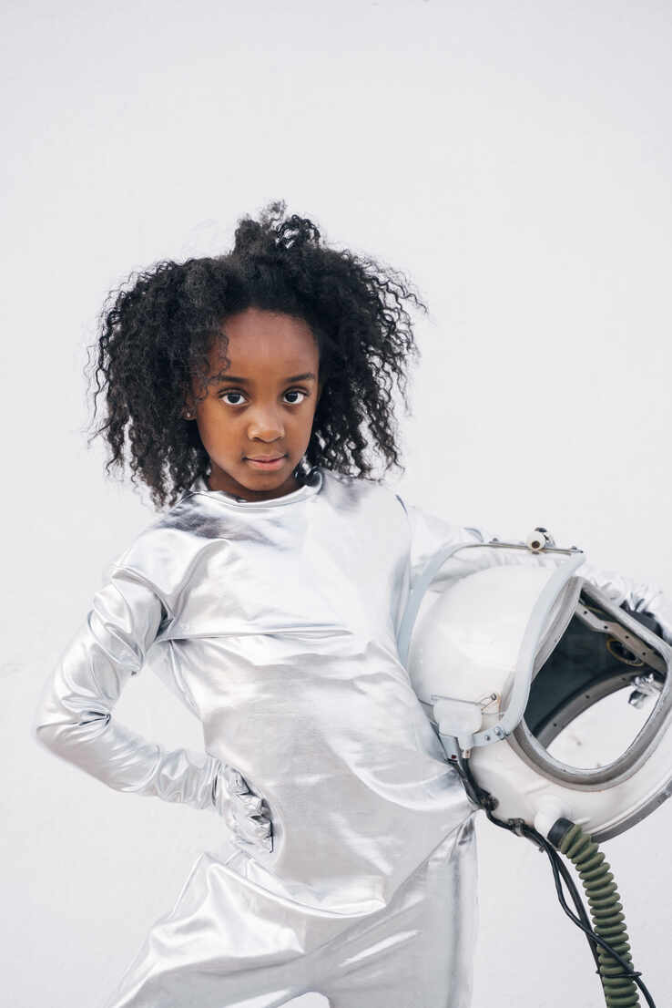 Portrait of little girl with space hat wearing space suit in front of white background - JCMF00068 - Jose Luis CARRASCOSA/Westend61