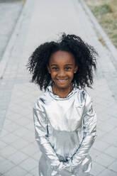 Portrait of happy little girl wearing space suit outdoors - JCMF00071