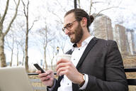 Smiling young businessman with coffee to go looking at cell phone, New York City, USA - MFRF01310
