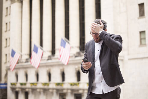 Astonished young businessman looking at cell phone in front of Stock Exchange, New York City, USA - MFRF01319