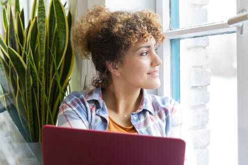 Woman with laptop looking out of window in office - FKF03375