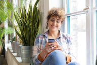 Smiling woman sitting at the window in office using cell phone - FKF03378
