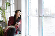 Woman looking out of window in office - FKF03381