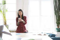 Woman using cell phone at the window in office - FKF03387