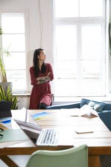 Woman looking out of window in office - FKF03390