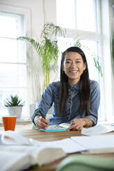 Portrait of happy woman working at table in office - FKF03405