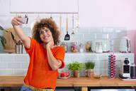 Happy woman taking a selfie in office kitchen - FKF03423
