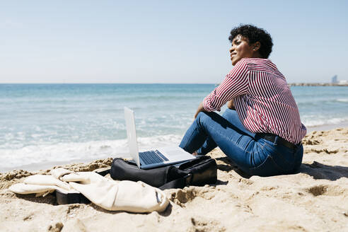 Woman sitting on the beach while working with the laptop - JRFF03321