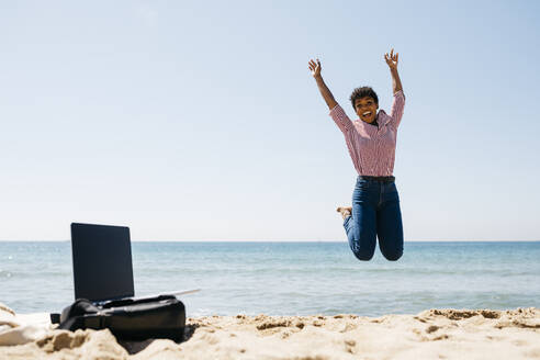 Woman jumping on the beach, laptop on bag - JRFF03324