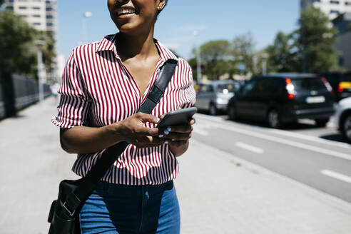 Woman using smartphone while walking in the city - JRFF03327