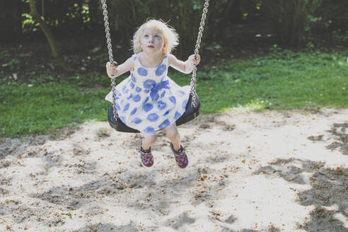 Portrait of blond little girl wearing summer dress sitting on a swing looking up - IHF00139