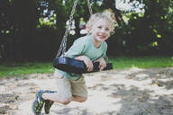 Portrait of little boy playing with swing - IHF00142