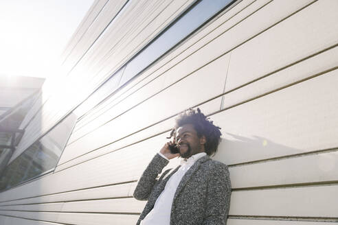 Businessman talking on cell phone outside office - AHSF00548