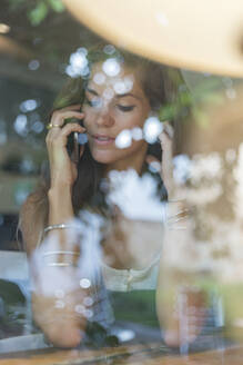 Young woman on cell phone behind windowpane of a cafe - JPTF00165