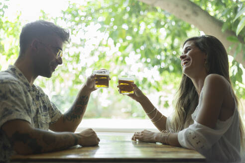 Happy young couple clinking beer glasses at the table of a restaurant - JPTF00171