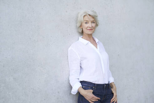 Portrait of relaxed mature woman wearing white shirt leaning against concrete wall - PNEF01725