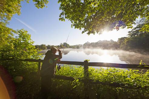 Fisherman carp fishing at dawn at fence along tranquil misty lake - JUIF01581