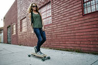 Mixed race woman riding skateboard on city street - BLEF07774