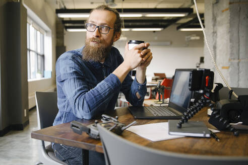 Thoughtful creative businessman drinking coffee in office - HEROF36536