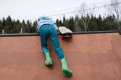 Boy clambering to top of skateboard ramp, rear view - ISF21544