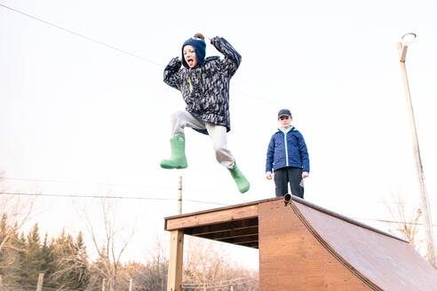 Girl watching brother jump from top of skateboard ramp - ISF21577