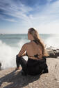 Young female surfer with long blond hair sitting on beach rock, rear view, Cape Town, Western Cape, South Africa - ISF21595