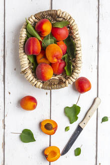 Apricots in basket, knife on white wood - SARF04317
