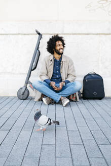 Spain, Barcelona. Pigeon walking down the street with a man sitting on the ground with his electric scooter next to him in the background - JRFF03348