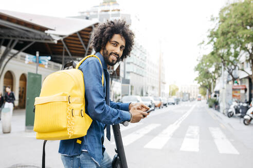 Portrait of smiling young man with backpack, E-Scooter and mobile phone in the city, Barcelona, Spain - JRFF03372