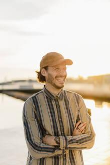 Prtrait of laughing man wearing baseball cap and stripes shirt at sunset - AFVF03338