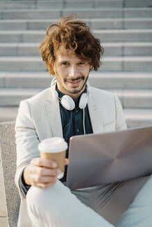 Portrait of businessman with coffee to go and laptop outdoors - AFVF03377