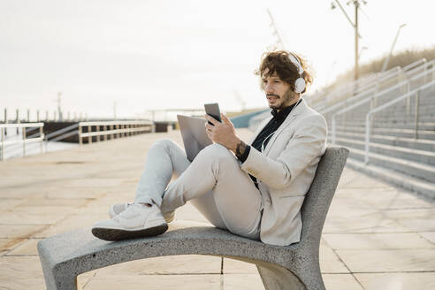 Portrait of shocked businessman with headphones and laptop looking at his mobile phone - AFVF03380