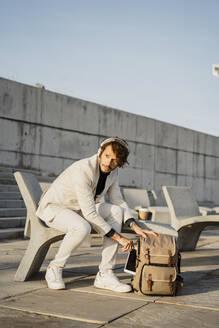 Portrait of businessman with headphones taking digital tablet out of backback - AFVF03386