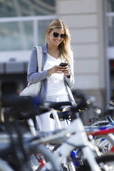 Young businesswoman texting with her mobile phone while walking - JSRF00287