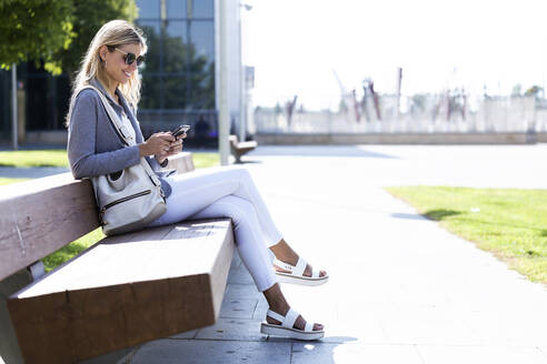 Young businesswoman texting with her mobile phone while sitting on bench - JSRF00290