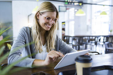 Young woman using her digital tablet while drinking coffee in the coffee shop - JSRF00293