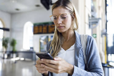 Young woman texting with her mobile phone in the train station hall - JSRF00299