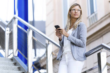 Young businesswoman texting with her mobile phone on stairs - JSRF00305