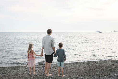 Back view of man standing hand in hand with little daughter and son at seafront - EYAF00253