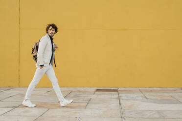 Portrait of walking businessman with backpack in front of yellow wall - AFVF03409